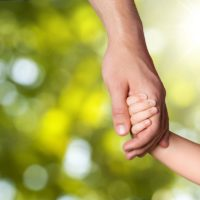 Father holding hands with child