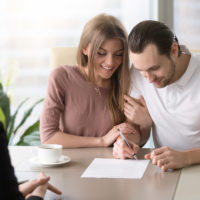 Happy family couple signing prenuptial agreement in presence of lawyer