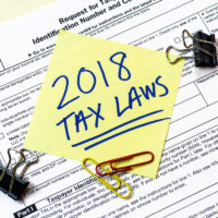 2018 tax laws sticky notes on top of w-9 tax form on desk with paper clips