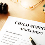 Child support agreement documents on top of desk with gavel, pen, glasses, and book