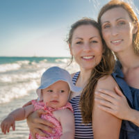 Same-sex couple with adopted baby on beach