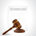 restraining order document behind gavel